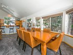 The dining table runs along a panel of windows and seats up to 8 guests.