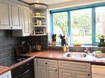 A well equipped kitchen caters for family needs,  with a view of the pretty, sheltered, patio garden