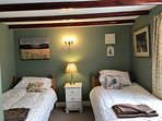 The cosy twin room has original beamed ceiling and a restful country theme.