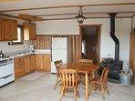 Kitchen, dining area, freestanding wood stove, and door to bathroom