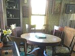 Wood dining and game table with assorted chairs.
