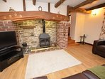Lounge with woodburner and steps up to dining room