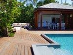 L'espace de vie extérieur se compose d'un grand deck, d'une piscine à débordement, et du salon