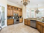 Open planned kitchen has granite counter tops and stainless steel appliances