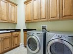 Laundry room with a washer, dryer, sink area, iron and ironing board