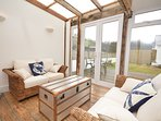Bright and airy sunroom with french doors out to enclosed garden