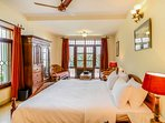 The bedroom on the ground floor with a king-size bed and opens up to the front porch