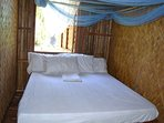 Bedroom one with queen bed and embedded mosquito net.