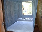 Bedroom 2 with full size bed and embedded mosquito net.