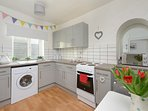 Kitchen with electric cooker/hob, mircowave,washer/dryer and a selection of pots, crockery etc.
