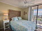 Carpeted master bedroom with queen bed, ceiling fan and private balcony access