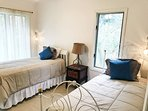 3rd bedroom has two twin beds, tiled floor and light curtains for a breezy feel.