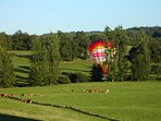 A hot air balloon taking off from the neighbouring field
