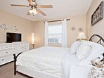 Master bedroom features a queen bed, ceiling fan, flat screen TV and access to private bathroom.