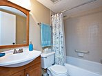 Guest bathroom with tub, shower and hand held shower head.
