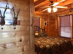 The cabin's second bedroom has a king-sized bed, wall-mounted LED TV, and full bathroom.