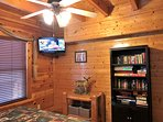 Cabin's second bedroom has a bookcase filled with games, puzzles and books.