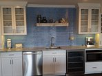 Wet bar has ice maker, microwave, dishwasher, fridge and variety of bar supplies and glassware.