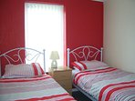 Twin Bedroom with two comfortable single beds ,Bedside cabinet and fitted wardrobe
