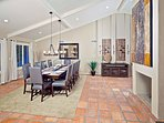 Formal dining room with fireplace and high ceilings.