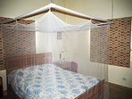 Queen-size bed with mosquito net (if needed) and Venetian blinds to darken the large room
