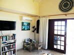 Living room. Smart TV, book shelf with many books to read, music dock; French door to terrace