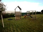 Play structure with nest swing, slide, climbing wall and monkey bars