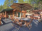 The patio, featuring a deck table,  outdoor grill, fire pit, and hot tub