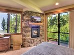 Gas fireplace, flatscreen TV, and lake views from the master bedroom