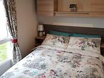 Master bedroom with double bed, overhead storage, lamps, large wardrobe, drawers, dressing table
