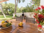 Porche Barbacoa y hamaca entre árboles en el jardín