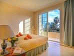 Guest bedroom with large door opening to balcony