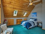 Warm wood paneling lines the vaulted ceiling in this queen bedroom.