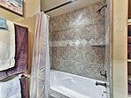 The bathroom hosts a shower/tub combo.