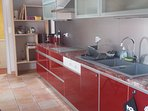 Espace cuisine: plaques à induction, lave-vaisselle, lave-linge, 2 réfrigérateurs, plaques induction