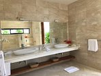 Luxury floor to ceiling marble ensuite w German tap ware, twin basins and garden views