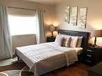 Master bedroom boasts a beautiful queen size bed.