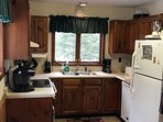 Country kitchen with all necessary utensils, pots and pans dishwasher, coffee pots, microwave