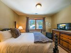 A TV is situated on the far end of the queen guest bedroom.