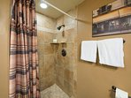 On the first floor, there's a guest bathroom with a tiled stand-alone shower.