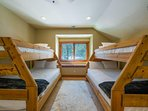 The bunk room has two large bunks made up of full and twin beds that sleep a total of 6 guests.