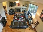 Top down view of living room area with open floor plan to kitchen and dining area behind