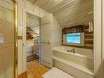 Shared Bathroom with large jetted tub, double vanity, and additional shower