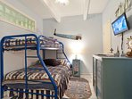 The guest bedroom has both twin-size and a full-size bed as bunks and a TV.