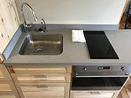 Large sink with adjacent induction cooktop with cookware provided.