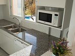 kitchen with dishwasher and pool and garden views-SA PUNTA COSTA BRAVA
