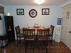 Kitchen table is bar height with 4 bar chairs, 2 bar stools are on inside wall area. Water disenser