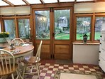 The conservatory/dining area looks onto the pretty garden