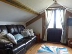 Wagon House Living room which is up stairs, has 2 large leather sofas with distant sea views