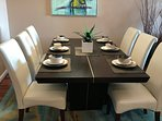 Dining room seats six and with 2 matching bar stools seats 8 hardwood floors and area trendy rug